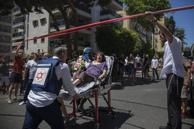 Israeli medics evacuate a woman from a targeted residential neighborhood Saturday where a rocket fired from the Gaza Strip hit the area, in Ramat Gan, central Israel.