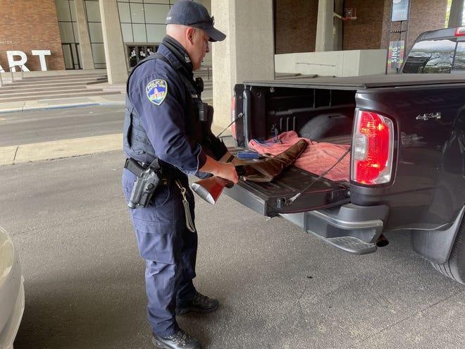 A Canton police officer collects a gun Saturday at the Canton Memorial Civic Center