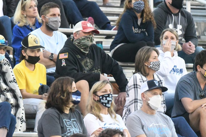 Fans wear masks while watching a Hoggard football game in March. New Hanover County lifted its mask mandate May 14. Health officials announced Tuesday that it's returning Friday for indoor places.
