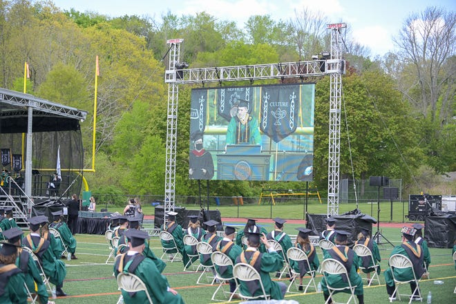 Nichols College seniors listen to keynote speaker Henry M. Thomas III during commencement exercises yesterday at the college in Dudley.