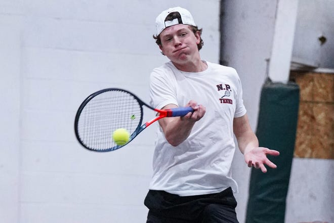 New Philadelphia's Elliott Warner explodes into a forehand during a match earlier this season.