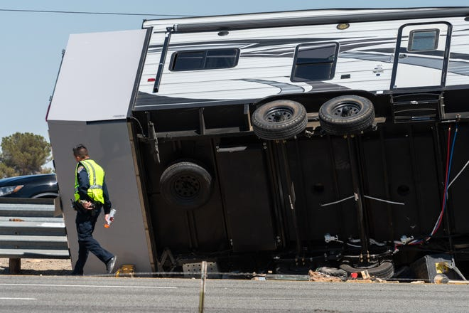 A California Highway Patrol officer walks next to a trailer on its side after a fatal crash on Interstate 15 in Hesperia on Saturday, May 15, 2021.
