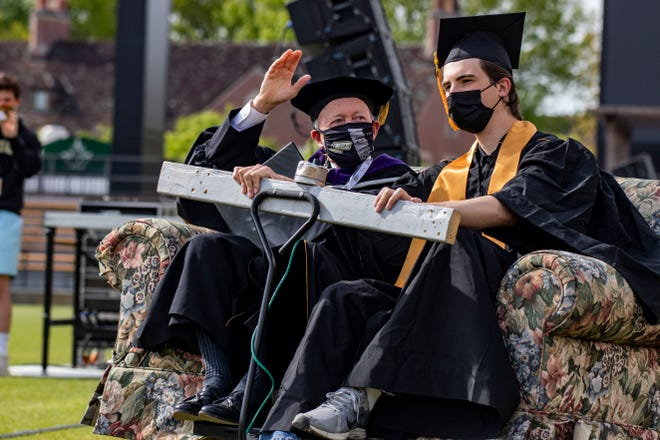"""Purdue President Mitch Daniels arrives to the 2021 Spring Commencement on a motorized couch with a Purdue candidate for graduation May 15, 2021, in Ross-Ade Stadium. """"If any class in Purdue history has earned this moment, it's you,"""" he said during his speech."""