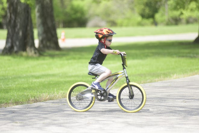 """Ethan Heck, 5, of Mansfield, works his way through a bicycle agility course Saturday morning at North Lake Park as part of the police department's """"Bike-A-Palooza"""" festival."""