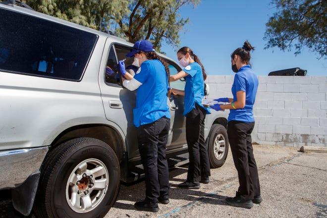 California State University San Bernardino nursing students Stephanie Gutierrez, left, and Jennifer Hanson administer the COVID-19 vaccine as Cidney Silva assists during a drive thru clinic in Desert Hot Springs, Calif., on Saturday, May 15, 2021.