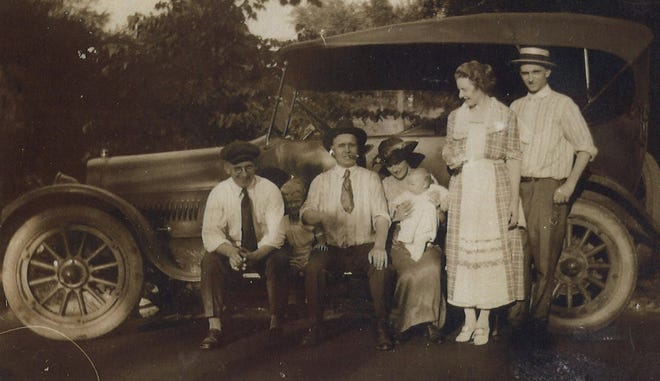 Family and friends hang out around an automobile in this photo from the 1920s.