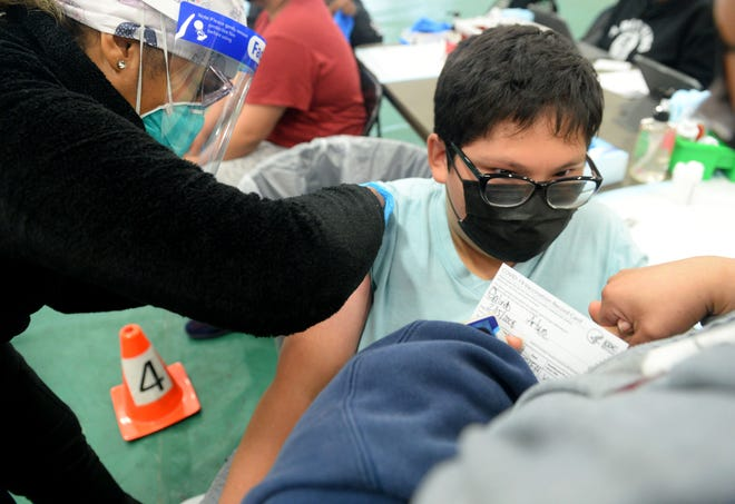Nurse Massiel Mejia gives Luis Galindo, 14, his COVID-19 shot at Pacifica High School in Oxnard on  May 15.  A group of students helped organize the vaccine clinic with Venture County health officials.