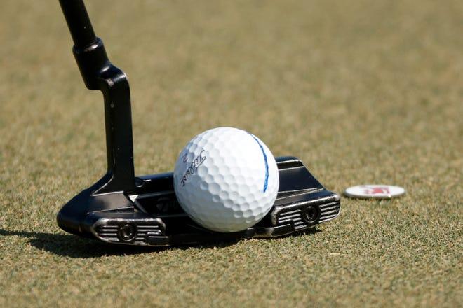 A detail view a golf ball and putter.