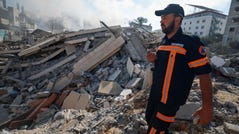 A member of the Palestinian civil defense walks amidst the rubble of a building in Gaza City which housed the Intaj Bank on Saturday, May 15, 2021. The institution is linked to Hamas, which controls the Gaza Strip.