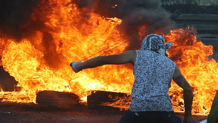 """A Palestinian protester uses a slingshot to hurl stones amid clashes with Israeli security forces near the Hawara checkpoint south of the occupied West Bank city of Nablus on May 15, 2021, as Palestinians commemorate the Nakba, the """"catastrophe"""" of Israel's creation in 1948, which turned hundreds of thousands into refugees."""
