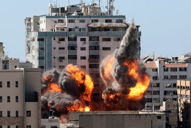 May 15, 2021: A ball of fire erupts from a building housing various international media, including The Associated Press, after an Israeli airstrike in Gaza City. The attack came roughly an hour after the Israeli military ordered people to evacuate the building, which also housed Al-Jazeera and a number of offices and apartments. There was no immediate explanation for why the building was targeted.