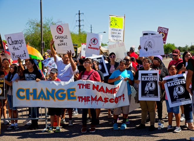 """Activists protest the Washington NFL team's nickname, formerly the Redskins, at a game in 2014. A state commission in Kansas recommended schools """"review and eliminate"""" the use of American Indian mascots, nicknames or imagery."""