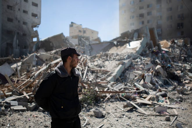 Palestinian policeman stands at rubble of a building destroyed by an Israeli airstrike that housed The Associated Press' offices in Gaza City, Saturday, May 15, 2021. The airstrike Saturday came roughly an hour after the Israeli military ordered people to evacuate the building. There was no immediate explanation for why the building was targeted. The building housed The Associated Press, Al-Jazeera and a number of offices and apartment.