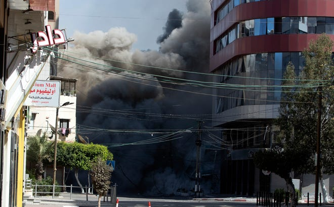 An Israeli airstrike hits the high-rise building that houses The Associated Press' offices in Gaza City, Saturday, May 15, 2021. The airstrike Saturday came roughly an hour after the Israeli military ordered people to evacuate the building. There was no immediate explanation for why the building was targeted. The building housed The Associated Press, Al-Jazeera and a number of offices and apartment.
