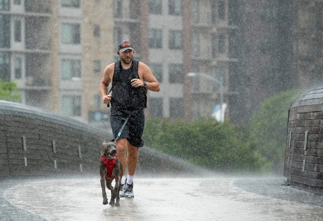Tyler Smestad runs in the rain across the Pfluger Bridge on Sunday. Weather in the area won't look much different over the next few days; Austinites can expect a wet week, according to the National Weather Service.