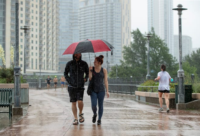 Michael Fernandez and Kaitlin Clancey walk in the rain on the Pfluger Bridge over Lady Bird Lake on May 16, when the city's main weather station at Camp Mabry recorded 1.09 inches of rain.