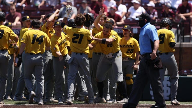 Missouri's Brandt Belk (21) is mobbed by teammates after hitting a pinch-hit grand slam during a game against Mississippi State on Saturday in Starkville, Miss.