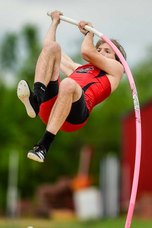 """Gavin Funk, Chillicothe High School sophomore, uses his strength, grip and approach speed to bend his vaulting pole and elevate him toward the bar several feet above him during Saturday's Class 3 District 8 track-and-field meet at Chillicothe's Jerry Litton Memorial Stadium II. Funk, having placed no higher than second in any regular-season meet and twice having been out of the team's lineup lately with nothing better than a best height of 10' (3.05m), dramatically established a new personal-best of 11'11"""" (3.65 meters) to win the event at district. The height is the best by a Hornet since Kyle Ross cleared 13'3"""" at state in 2016."""