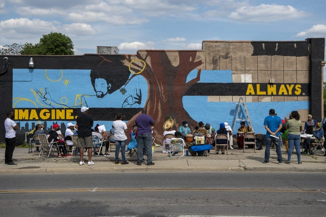 """Poet and former member of the Uhuru Dance Company, Charles """"Is Said"""" Lyons, unveils a mural celebrating the organization's contributions to the community."""