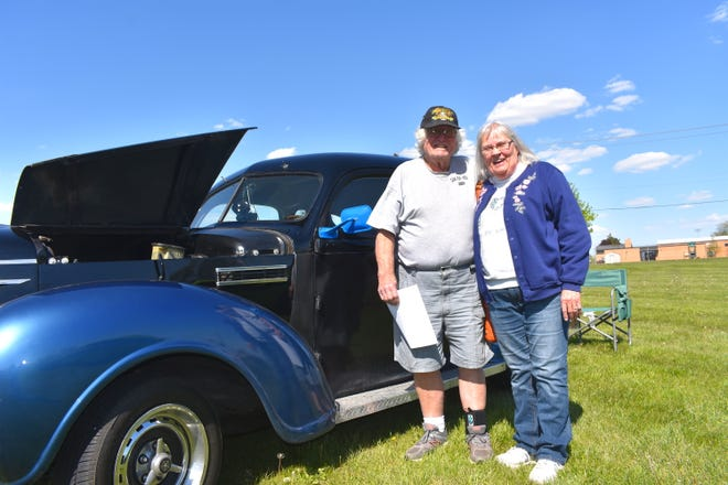 Hudson residents Jerry and Ella Green stand in front of their 1939 Plymouth P-8 Friday afternoon during the first installment of the 2021 Winter Street Plaza car show in Adrian. The monthly car show, operated by Street Machines of Lenawee, debuted Friday.