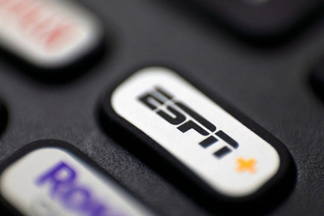 """FILE — This Aug. 13, 2020 file photo shows a logo for ESPN on a remote control, in Portland, Ore. The sports media giant announced Wednesday, Nov. 5, 2020, that it is cutting about 500 jobs from its global workforce and laying off approximately 300 employees. The company said the cuts are due in large part to the impact of the coronavirus pandemic on its business and the """"tremendous disruption in how fans consume sports.""""    (AP Photo/Jenny Kane, FIle)"""