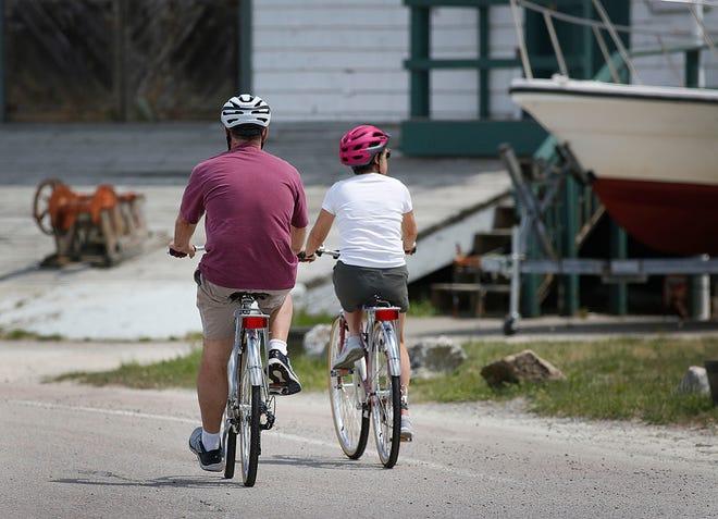 A pair of bike riders pedal along Nantasket Avenue on Sunday, May 15, 2021.