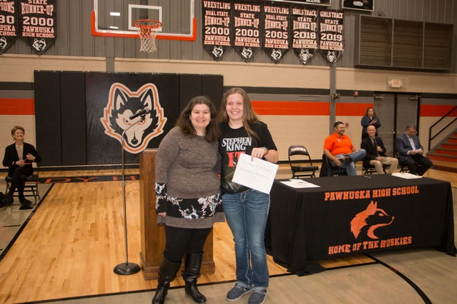 Libby Strahan, left, presents the $300 PEO Chapter EM Scholarship to Tennessee McCartney during Pawhuska High School's Awards Assembly for juniors and seniors on May 10. McCartney graduated May 14 with the Class of 2021.