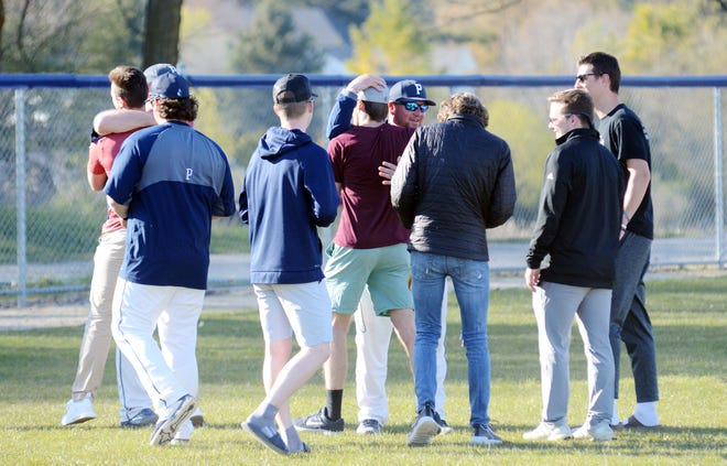 Members of the 2020 senior class are embraced by Petoskey head coach Shawn Racignol (back, middle) and assistant coach Mike Loper after they got the chance to take Turcott Field one last time to throw out the first pitch Friday night.