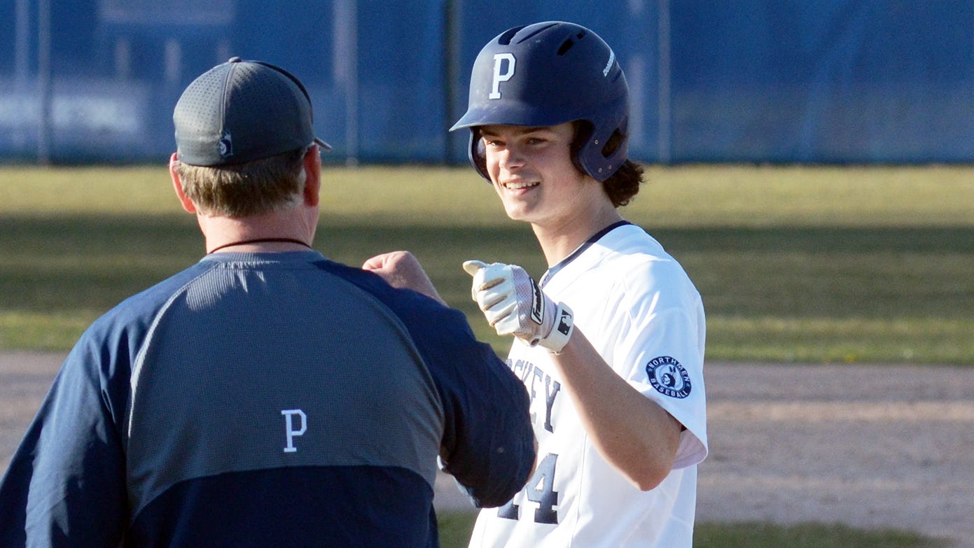 Petoskey's Owen DeGroot celebrates on first base with coach Mike Loper after a solid hit.