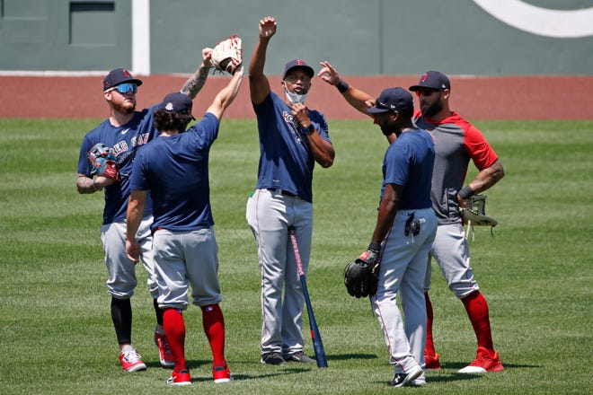 """The Red Sox's Tom Goodwin, middle, celebrates with players after a workout at Fenway Park earlier this season. """"It helps to have a smile on your face when you're on the field,"""" says the first-base coach."""