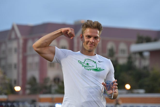 Oregon decathlete Max Vollmer flexes and poses with his championship trophy Saturday during the Pac-12 Track & Field Championship meet in Los Angeles.