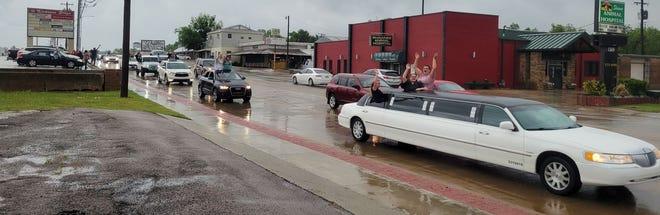 Shawnee High School seniors wave as the parade passes along Kickapoo.