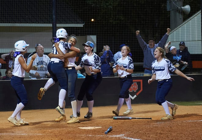 Maddie Scanlan (left) is lifted in the air by Icess Tresvik after Scanlan scored the game-winning run Saturday as Hoggard clinched the state title with a 6-5 victory over East Forsyth. [Bruce Chapman/Special to the StarNews]