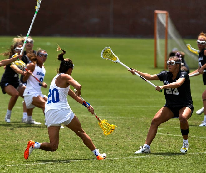 Florida attack Brianna Harris (20) with a shot on goal in the first half Sunday against Jacksonville during the second round the NCAA women's lacrosse tournament at Donald R. Dizney Stadium.