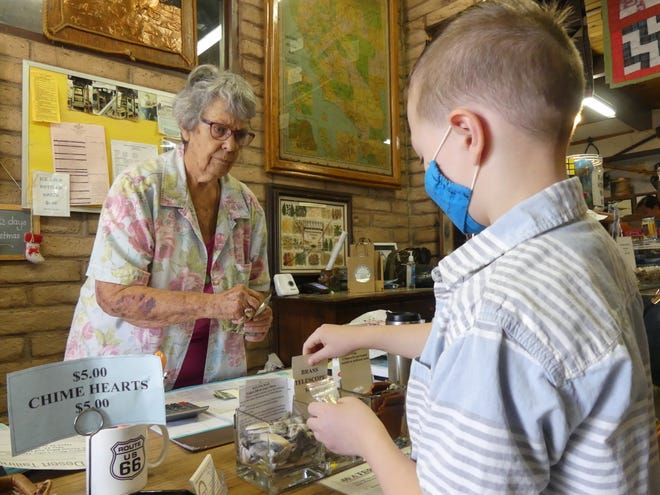 """Mojave River Valley Museum Committee Chairwoman and docent Pat Schoffstall helps a young historian during the museum's """"54th Annual Barbecue and Open House"""" in Barstow earlier this year."""