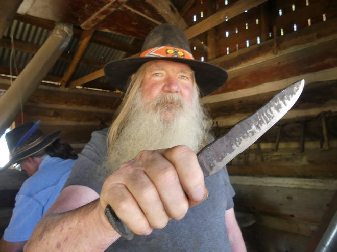 """Blacksmith Klaus Deubbert, 70, displays a forged knife for a visitor at the Mojave River Valley Museum's """"54th Annual Barbecue and Open House"""" on Saturday in Barstow."""