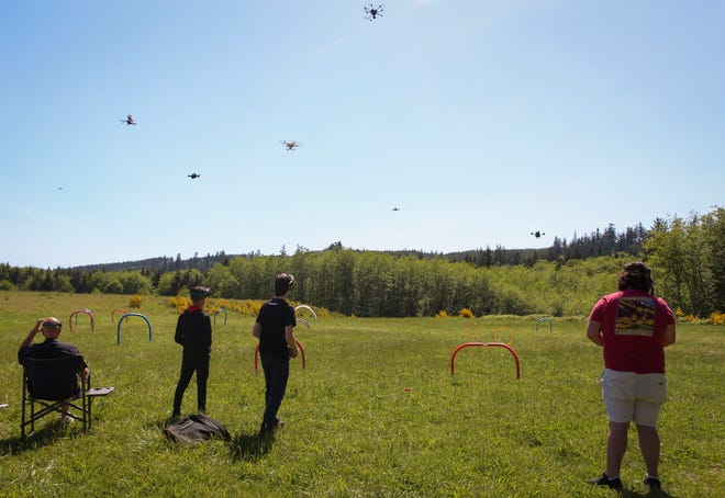 Drone enthusiasts hover their drones in their air at Port Gamble RC Field during a Saturday picnic hosted by the Kitsap Drones group.