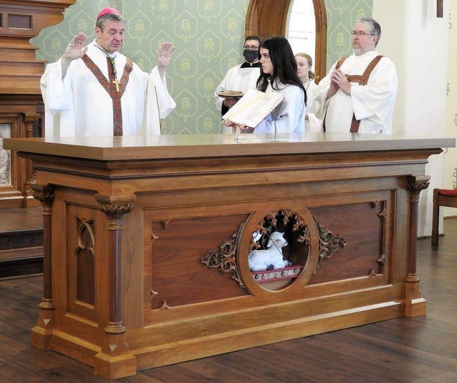 Bishop Robert Brennan of the Columbus Dioceses performs a dedication of a new altar Sunday at Sacred Heath Catholic Church with assistance from Jillian Given and Deacon Dave Lozowski.