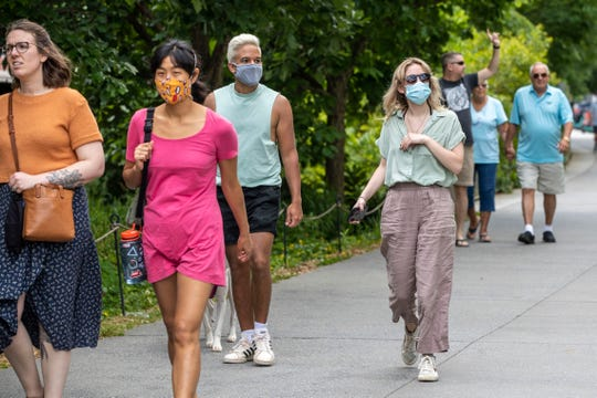 Madeline Rascai, right, and Aldani Diaz, third from left, wear face masks as they walk along the Attlanta BeltLine in the Old Fourth Division community of Atlanta, Friday, May 14, 2021. They both say they are fully vaccinated. but still prefer to wear face masks while in public.
