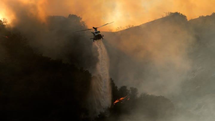 A firefighting helicopter drops water onto a brush fire in the Pacific Palisades area of Los Angeles on Saturday, May 15, 2021.