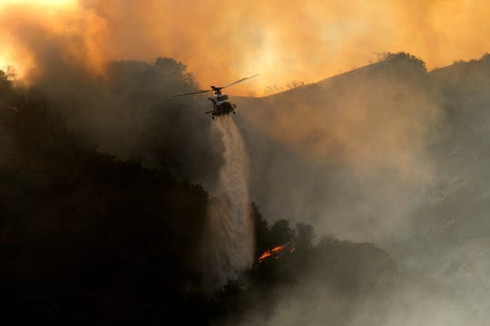 A firefighting helicopter puts water on fire with a brush in the Pacific Palisade area of Los Angeles on May 15, 2021.