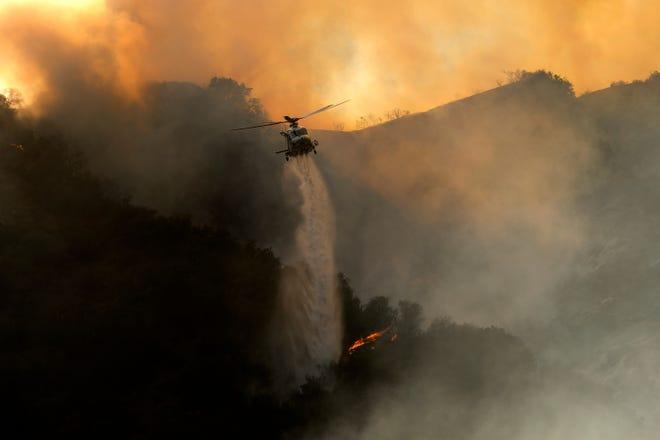 15 मई, 2021 को लॉस एंजिल्स के पैसिफिक पालिसैड्स क्षेत्र में एक अग्निशामक हेलीकॉप्टर ब्रश की आग पर पानी गिराता है।
