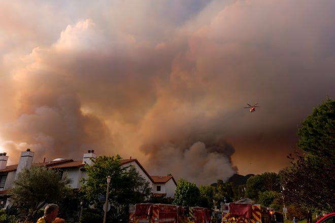 A firefighting helicopter drops water on a brush fire scorching at least 100 acres in the Pacific Palisades area of Los Angeles on  Saturday, May 15, 2021.