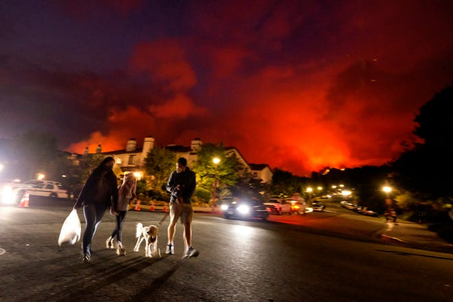 Residents walk a dog as a brush fire burns behind homes in the Pacific Palisades area of Los Angeles on Saturday, May 15, 2021.