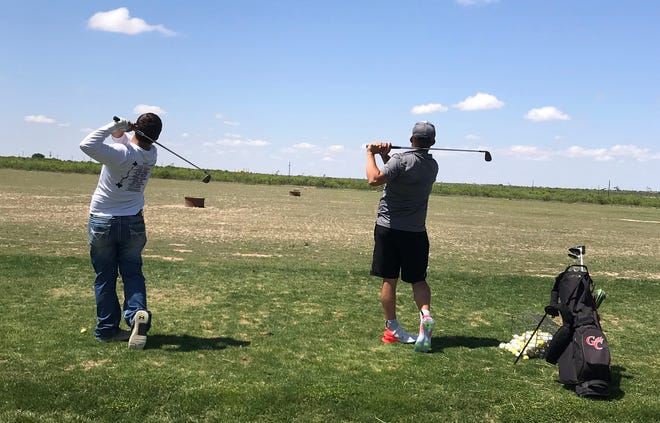 Garden City High School golfers hit balls at the driving range in town. Despite not having a golf course in town, the Bearkats' girls and boys teams have enjoyed an incredible amount of success.