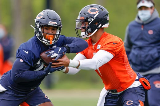 Chicago Bears quarterback Justin Fields (1) hands the ball to running back Khalil Herbert (24) during rookie minicamp at Halas Hall on May 15.