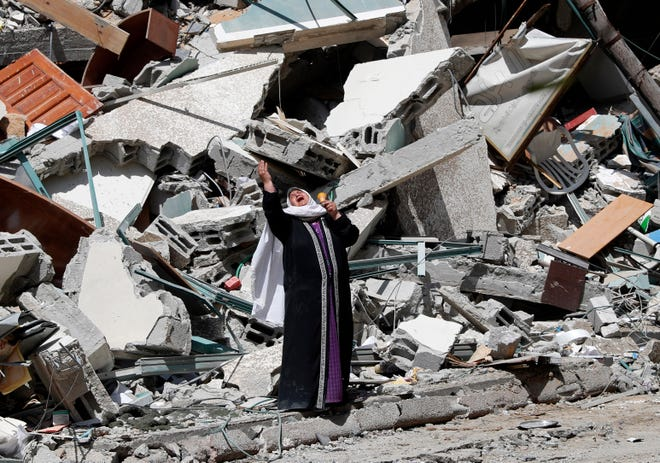 A woman stands near the rubble of a building in Gaza City destroyed by an Israeli air strike May 15. The building housed offices of The Associated Press, broadcaster Al-Jazeera and other media outlets.