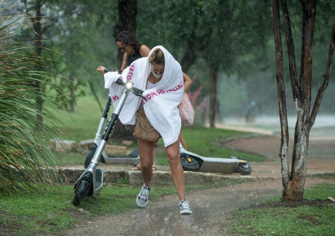 Vanessa Alvarez gets caught in heavy rain while riding a scooter along South Congress Avenue on Monday May 17, 2021.