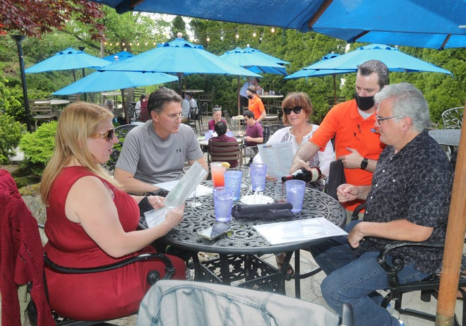 Bartender Michael Clark pours a Pinot Noir for a group of patio diners at the Blue Canyon on Saturday in Twinsburg.