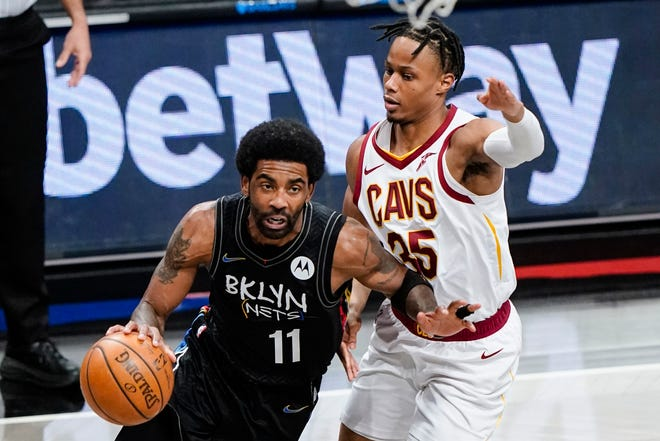 Brooklyn Nets' Kyrie Irving (11) drives past Cleveland Cavaliers' Isaac Okoro (35) during the first half of an NBA basketball game Sunday, May 16, 2021, in New York. (AP Photo/Frank Franklin II)